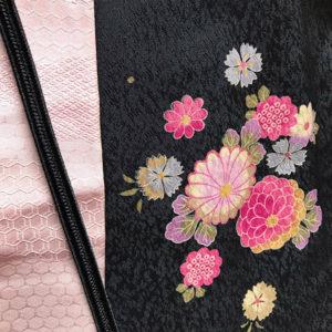 ピンクの帯揚げと黒の帯締めと着物の一揃い